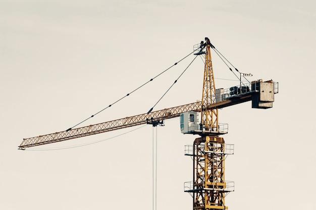 Gru a torre grande contro il cielo nei toni sbiaditi. primo piano dell'attrezzatura per l'edilizia con copyspace. costruire della città. Foto Premium