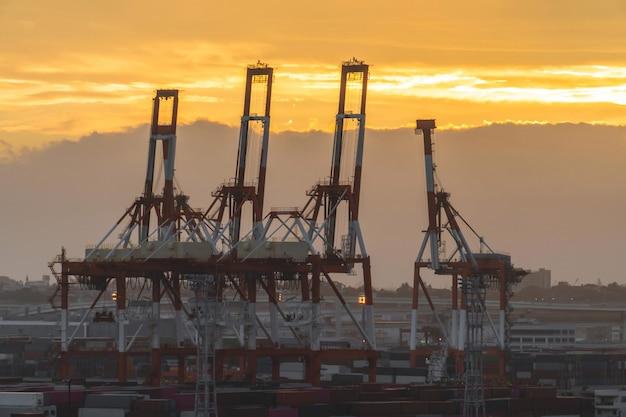 Gru del porto del porto industriale nel tramonto Foto Premium