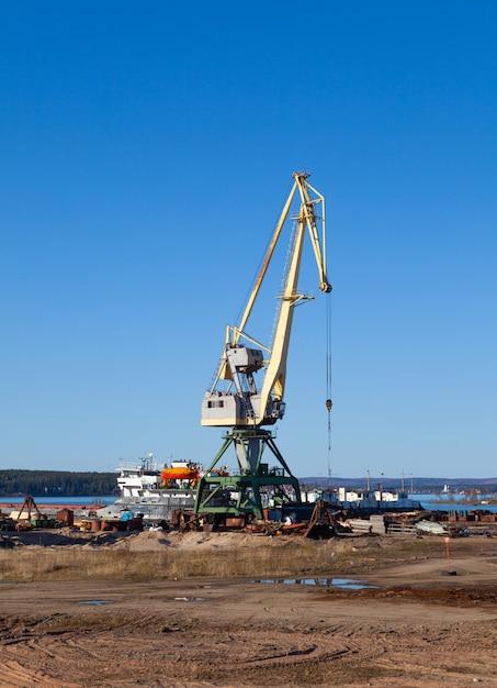 Gru nel porto di macchinari e carrelli elevatori per caricare e scaricare pallet in una soleggiata giornata estiva Foto Premium