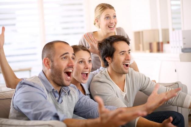 Gruppo allegro di amici che guardano partita di football americano in tv Foto Premium