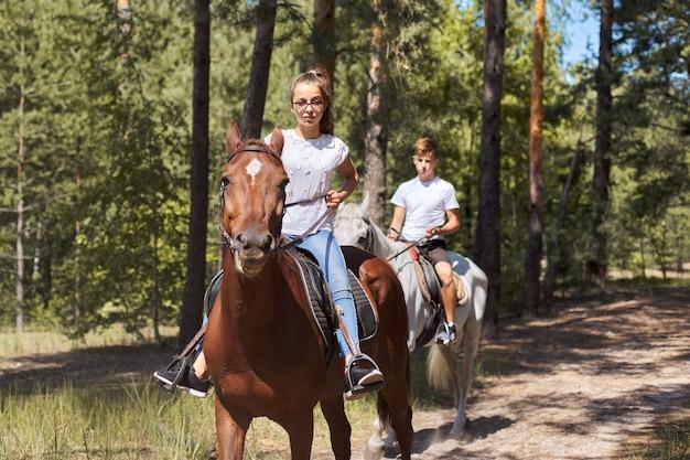 Gruppo di adolescenti a cavallo nel parco estivo Foto Premium