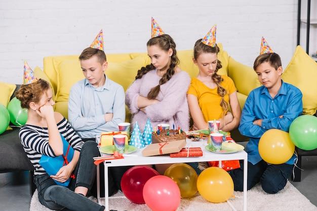 Gruppo di amici annoiati che si siedono nella festa di compleanno Foto Gratuite