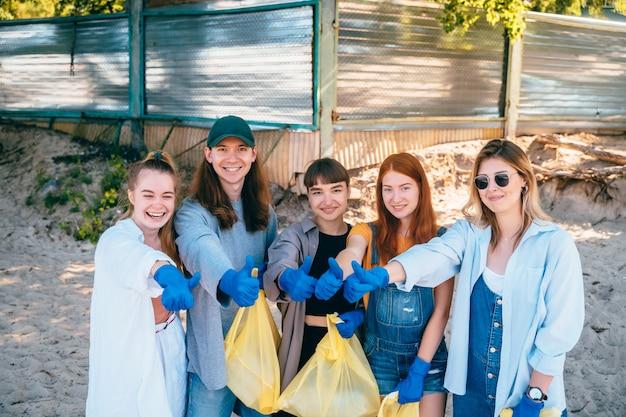 Gruppo di amici attivisti che raccolgono rifiuti di plastica sulla spiaggia. i ragazzi mostrano il pollice in su. Foto Gratuite