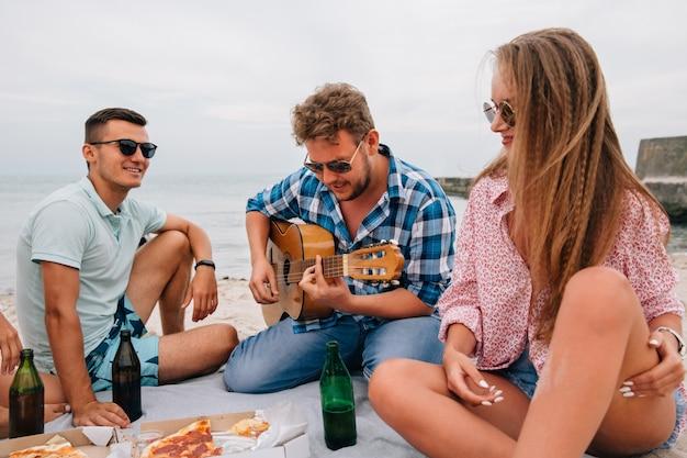 Gruppo di amici attraenti con un pic-nic, suonare la chitarra sulla spiaggia, mentre si mangia la pizza Foto Gratuite