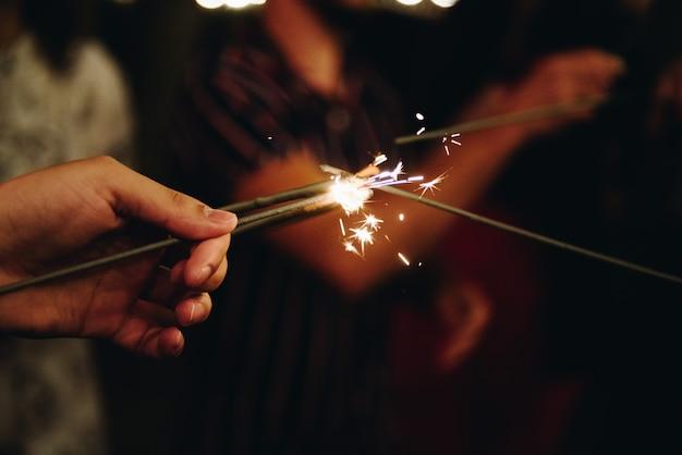 Gruppo di amici che accendono insieme le luci del bengala. amicizia. Foto Premium