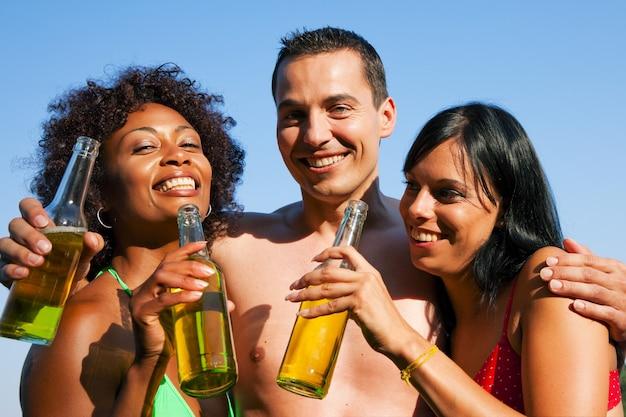Gruppo di amici che bevono birra in costume da bagno Foto Premium