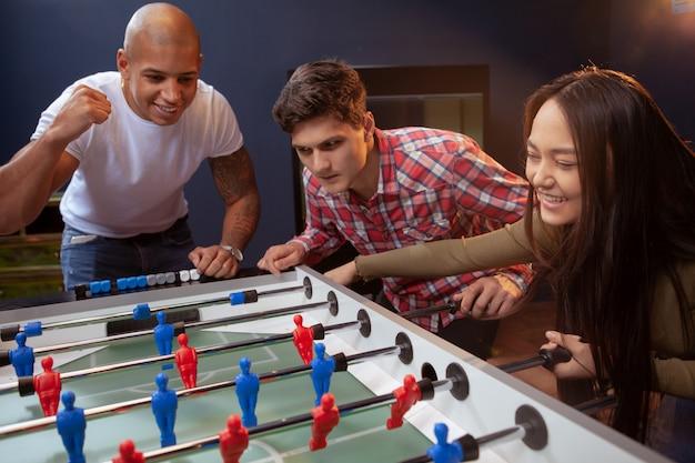 Gruppo di amici che giocano a calcio balilla al pub della birra Foto Premium