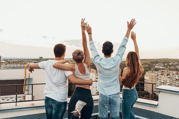 Gruppo di amici che godono all'aperto sul tetto Foto Gratuite