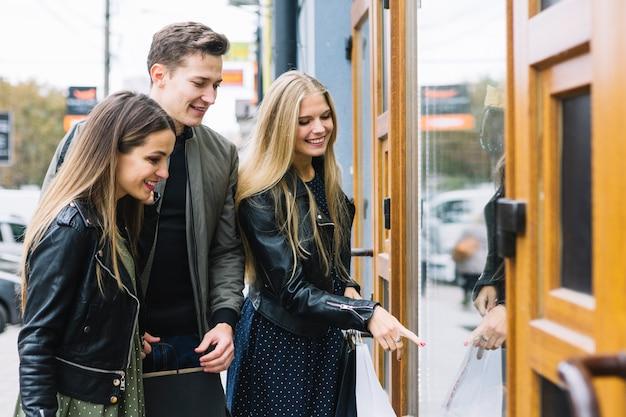 Gruppo di amici che godono lo shopping della finestra Foto Gratuite