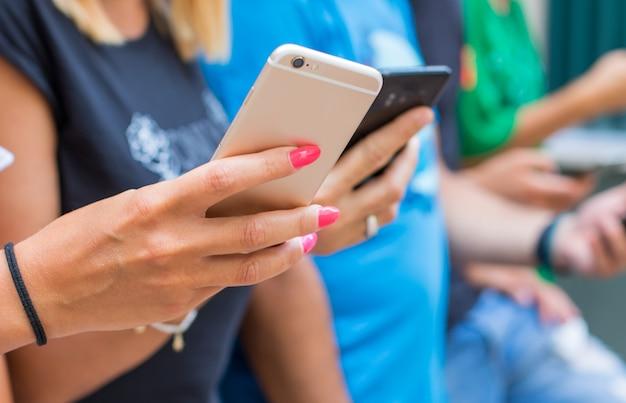 Gruppo di amici che guardano i telefoni cellulari intelligenti - generazione dei millennial Foto Premium