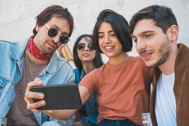 Gruppo di amici che prendono un selfie con il telefono. Foto Premium
