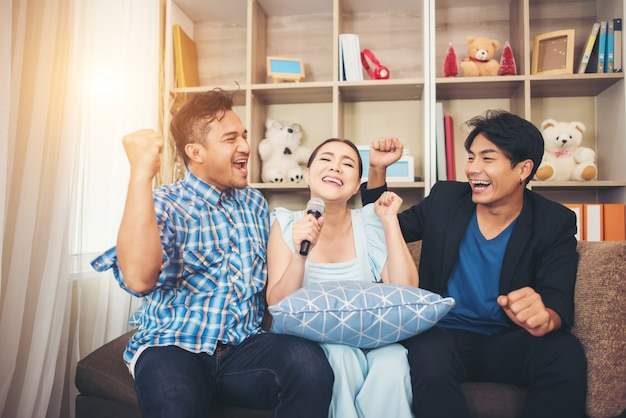 Gruppo di amici che si diverte in salotto a cantare insieme una canzone Foto Gratuite