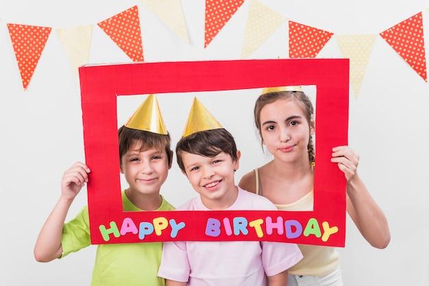 Gruppo di amici che tengono il cappello da portare del partito della struttura di buon compleanno Foto Gratuite
