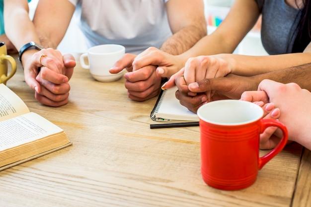 Gruppo di amici che tengono le mani sul tavolo con libri e tazze di bevanda Foto Gratuite