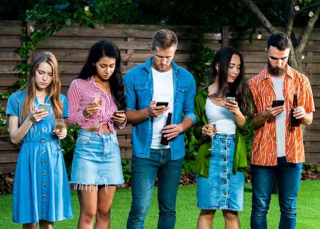 Gruppo di amici con smartphone all'aperto Foto Gratuite