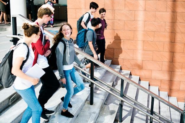 Gruppo di amici della scuola che cammina giù per la scala Foto Premium