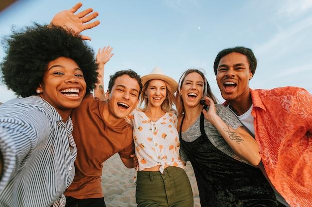 Gruppo di amici diversi prendendo un selfie in spiaggia Foto Premium