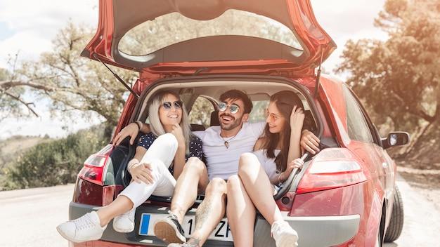 Gruppo di amici facendo divertimento nel bagagliaio della macchina sulla strada Foto Gratuite
