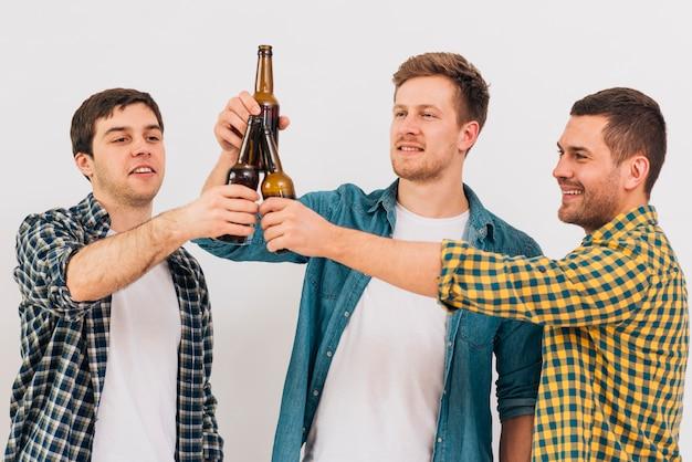 Gruppo di amici felici che tostano le bottiglie di birra contro fondo bianco Foto Gratuite