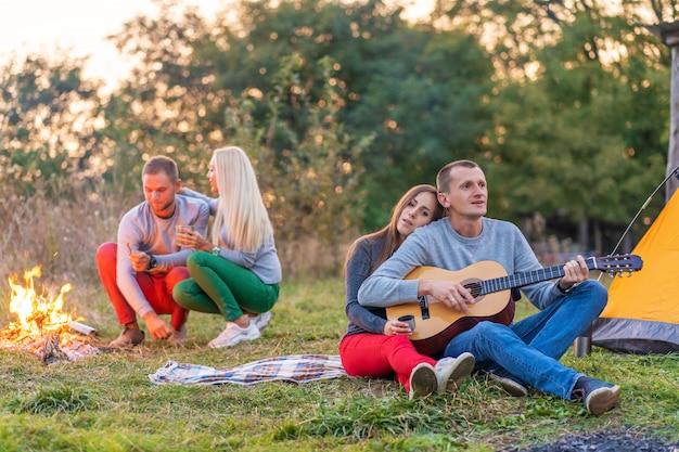 Gruppo di amici felici con la chitarra, divertirsi all'aperto, vicino al falò e tenda turistica. divertimento in campeggio famiglia felice Foto Premium