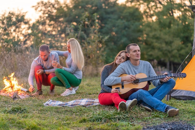 Gruppo di amici felici con la chitarra, divertirsi all'aperto, vicino al falò e tenda turistica. Foto Premium