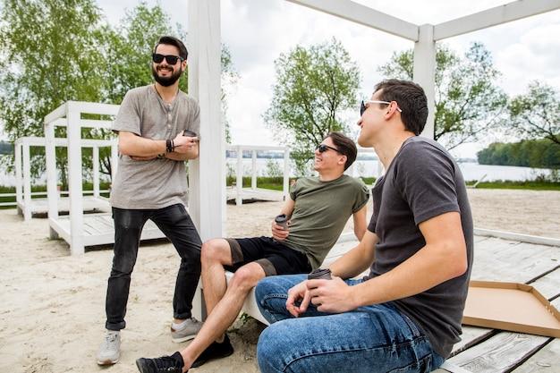 Gruppo di amici gioiosi che riposano in pergolato sulla spiaggia Foto Gratuite