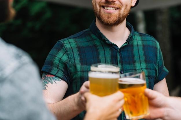 Gruppo di amici maschi che celebrano con un bicchiere di birra Foto Gratuite