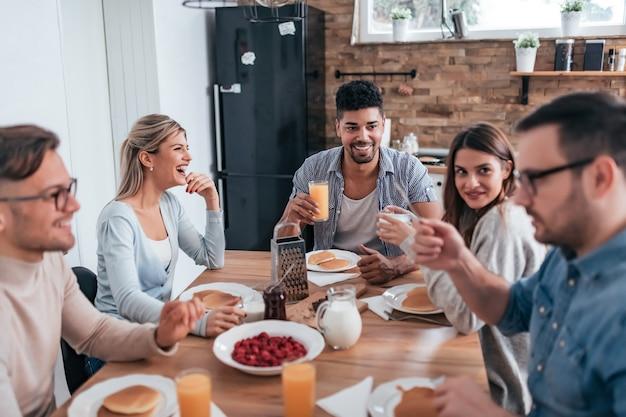 Gruppo di amici multietnici che mangiano i pancake per la prima colazione e che si divertono a casa. Foto Premium