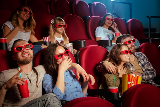 Gruppo di amici seduti in cinema con popcorn e bevande Foto Premium