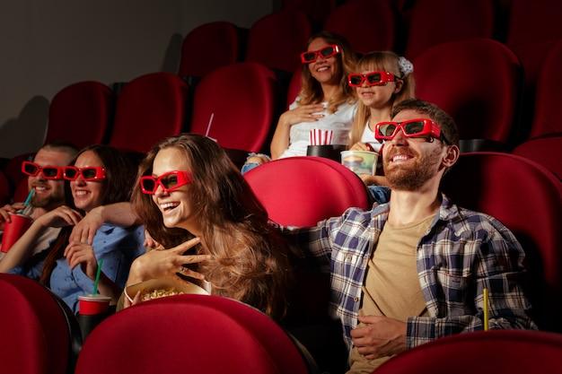 Gruppo di amici seduti nel cinema con popcorn e bevande Foto Premium