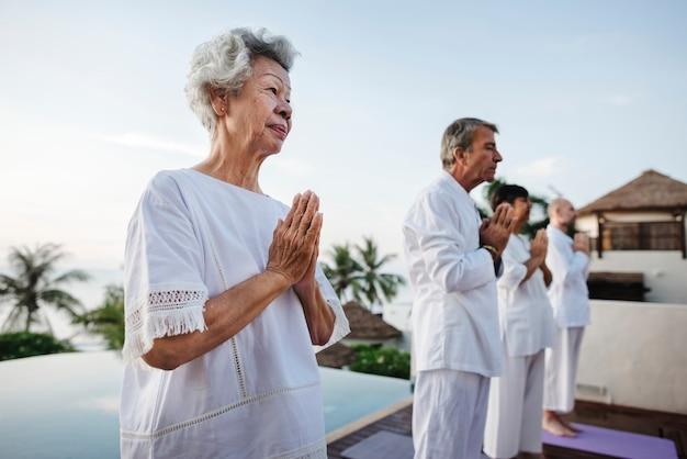 Gruppo di anziani che praticano yoga a bordo piscina Foto Premium