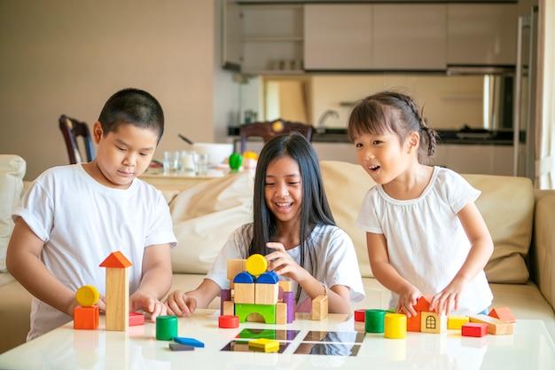 Gruppo di bambini asiatici che giocano insieme giocattolo a casa, concetto asiatico dei bambini Foto Premium