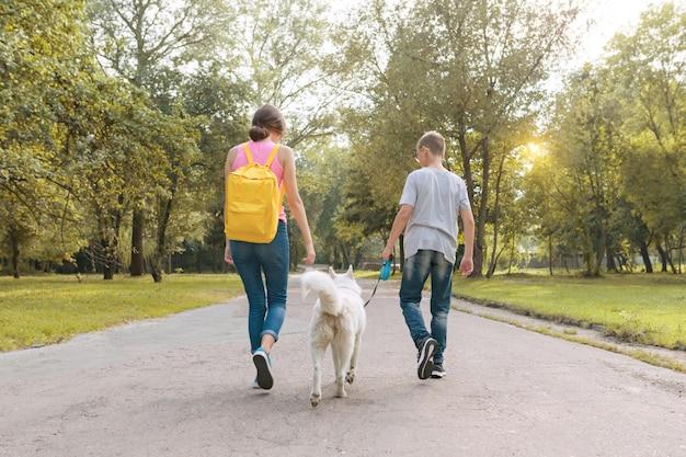 Gruppo di bambini che camminano con il cane husky bianco Foto Premium