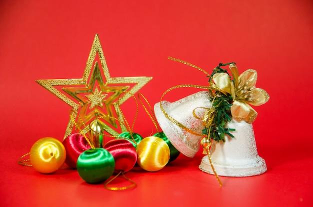Gruppo di campana, palla e regalo di natale su sfondo rosso Foto Premium