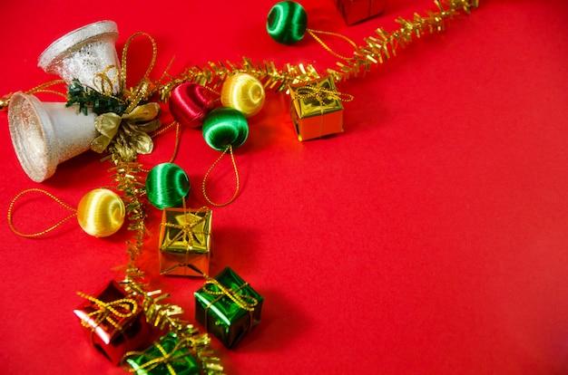 Gruppo di campana, palla e regalo nel natale su fondo rosso sulla vista superiore Foto Premium