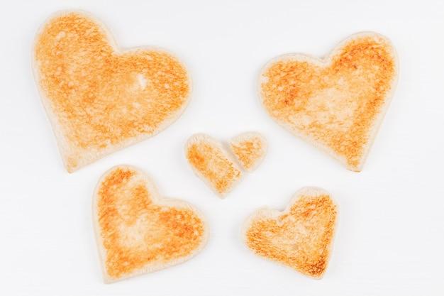 Gruppo di cuori di pane tostato con un cuore spezzato insieme su sfondo bianco Foto Premium