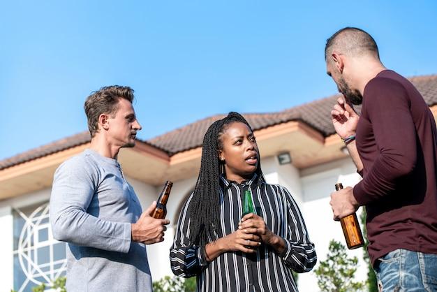 Gruppo di diversi amici che bevono alcolici nel cortile Foto Premium