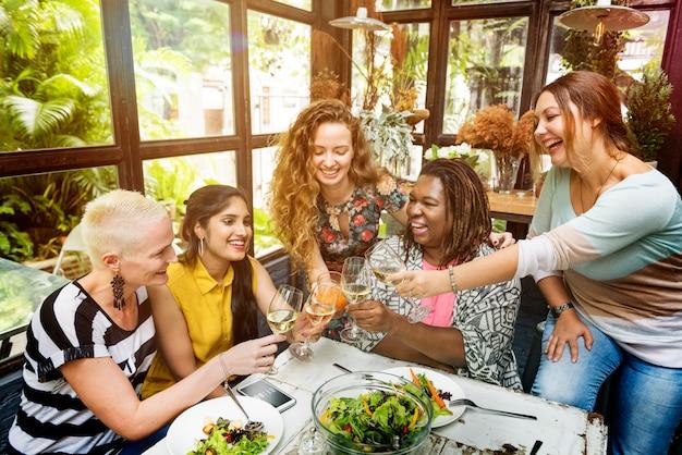 Gruppo di donne di diversità che appende mangiando concetto insieme Foto Premium