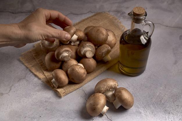 Gruppo di funghi portobello su un panno di rafia accanto a un barattolo di olio Foto Premium