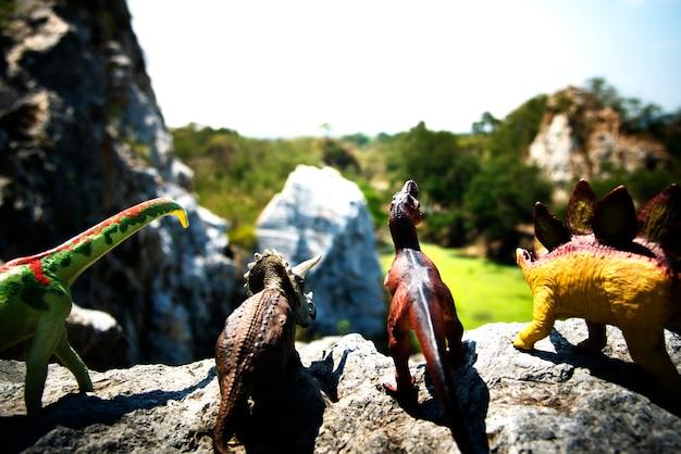 Gruppo di giocattoli di dinosauro su una roccia Foto Gratuite