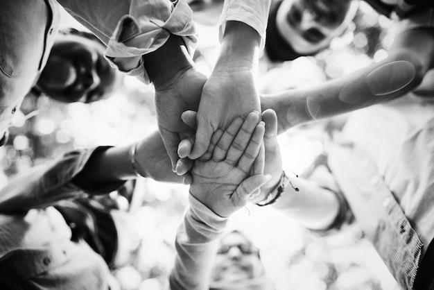 Gruppo di giovani amici accatastamento mani Foto Gratuite