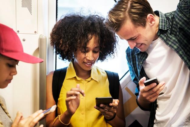Gruppo di giovani amici adulti che utilizzano gli smartphone nella metropolitana Foto Premium