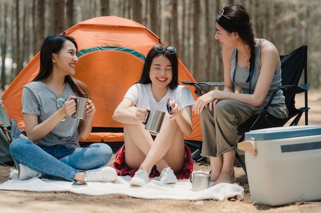 Gruppo di giovani amici asiatici campeggio o picnic insieme nella foresta Foto Gratuite