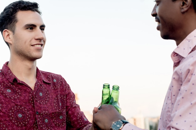 Gruppo di giovani amici con pizza e bottiglie di bevanda Foto Premium