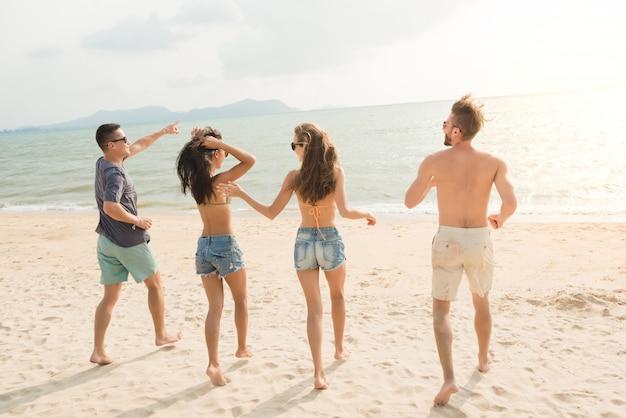 Gruppo di giovani amici felici che corrono dalla spiaggia al mare Foto Premium