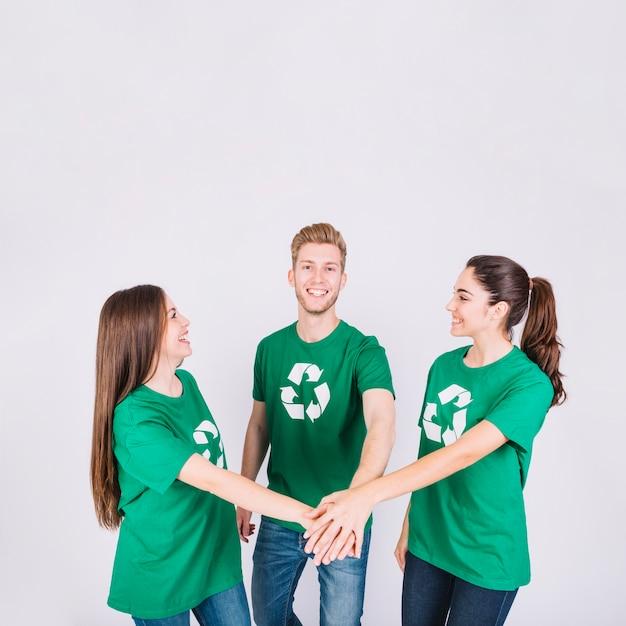 Gruppo di giovani amici felici che impilano le loro mani Foto Gratuite