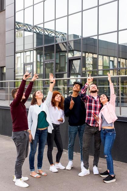 Gruppo di giovani amici in piedi sulla strada che punta verso l'alto davanti a un edificio moderno Foto Gratuite