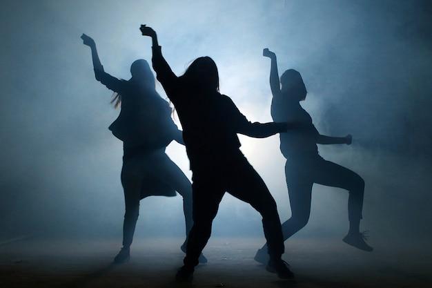 Gruppo di giovani ballerine femminili sulla strada di notte. Foto Premium