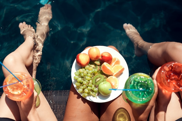 Gruppo di giovani belle donne che si siedono a bordo piscina Foto Premium