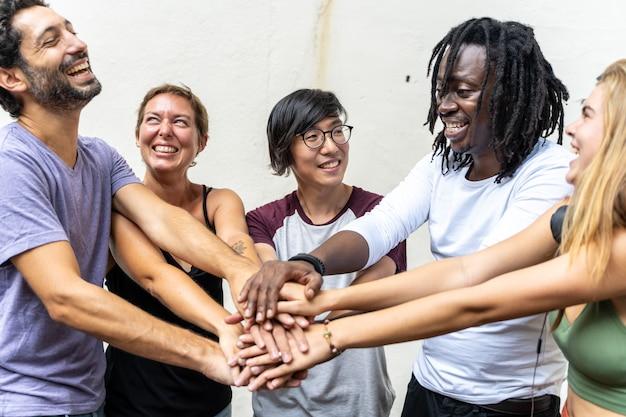 Gruppo di giovani di diverse etnie che sorridono e che uniscono la mano Foto Premium